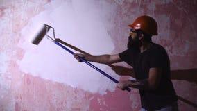 Casa de la pintura del hombre en concepto de DIY Hombre joven en la pared de la pintura con el rodillo almacen de metraje de vídeo