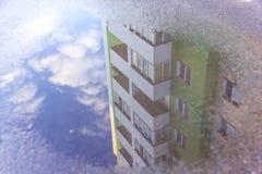 Casa de la reflexión del agua en el charco La construcción de viviendas es refl Fotos de archivo libres de regalías