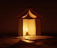 Casa de libros con la luz de la vela fotos de archivo