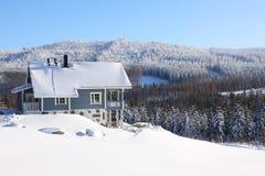 Casa de log na neve no sunhine Imagens de Stock