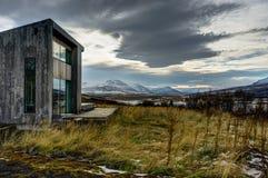 Casa de Lolla del chalet cerca de Akureyri con la hierba amarilla y el cielo nublado Fotos de archivo