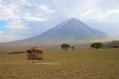 Casa de Maasai con el volcán en fondo Imagen de archivo libre de regalías