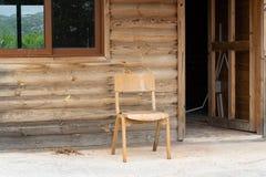 Casa de madeira abandonada velha com cadeira fora foto de stock