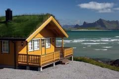 Casa de madeira amarela com telhado da grama imagens de stock