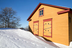 Casa de madeira amarela rural na estação do inverno Fotos de Stock