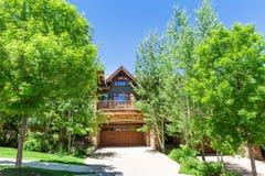 Casa de madeira com as árvores em torno dela no dia ensolarado imagens de stock royalty free