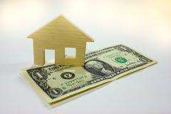 Casa de madeira com dinheiro do dólar Imagem de Stock