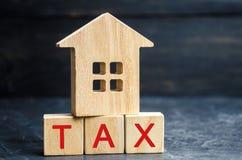 Casa de madeira com a inscrição 'imposto ' Impostos em bens imobiliários, pagamento Pena, atrasos Registro dos contribuintes para imagem de stock royalty free