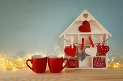 Casa de madeira com muitos corações ao lado dos copos de café Foto de Stock Royalty Free