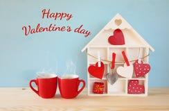 Casa de madeira com muitos corações ao lado dos copos de café Imagens de Stock Royalty Free