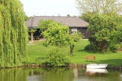 Casa de madeira com o jardim ao longo do canal e do barco, NL Fotografia de Stock Royalty Free