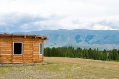 Casa de madeira da montanha no campo verde Montanhas, Altay, Rússia Fotografia de Stock Royalty Free
