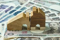 Casa de madeira diminuta na pilha de cédulas do iene japonês como o fina Fotos de Stock