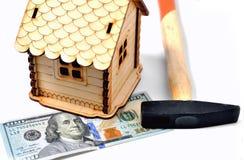 Casa de madeira do brinquedo, uma cédula de 100 dólares e um martelo em um wh Imagem de Stock