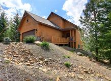 Casa de madeira do estilo da cabine no monte rochoso com garagem Imagem de Stock