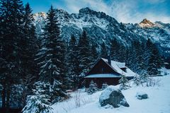 Casa de madeira do feriado das férias do inverno nas montanhas cobertas com a neve e o céu azul fotos de stock