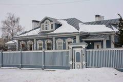 Casa de madeira do russo idoso com quadros e a cerca cinzelados de janela Fotografia de Stock Royalty Free