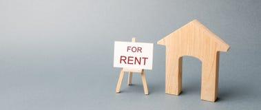 Casa de madeira e um cartaz com a inscrição para o aluguel O conceito de alugar uma casa ou um apartamento para o aluguel Carca?a fotografia de stock royalty free