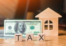 Casa de madeira e uma conta de cem dólares, impostos da inscrição Conceito dos impostos sobre os bens imóveis, da compra e da ven Foto de Stock Royalty Free