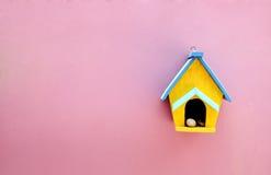 Casa de madeira feito a mão na parede cor-de-rosa Fotos de Stock Royalty Free