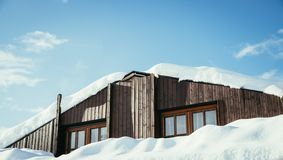 Casa de madeira moderna com janelas e neve no telhado, céu azul com espaço do texto imagem de stock royalty free
