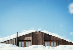 Casa de madeira moderna com janelas e neve no telhado, c?u azul com espa?o do texto imagens de stock royalty free