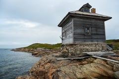 Casa de madeira na costa, norte, Rússia Fotografia de Stock