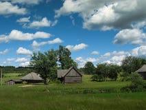 Casa de madeira na grama e nas nuvens do céu da árvore da natureza em Letónia 2014 Foto de Stock
