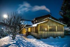 Casa de madeira na neve na noite do inverno Imagem de Stock Royalty Free