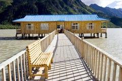 Casa de madeira no lago perto da montanha Fotografia de Stock Royalty Free