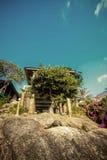 A casa de madeira pequena é construída em pilhas sob a rocha E fotografia de stock