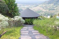 Casa de madeira redonda da cabana do telhado nos montes verdes Foto de Stock