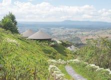 Casa de madeira redonda da cabana do telhado nos montes verdes Imagem de Stock Royalty Free