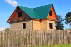 Casa de madeira sob a construção atrás da cerca Imagem de Stock