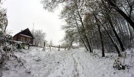 Casa de madeira velha em uma estrada coberto de neve através das árvores Foto de Stock