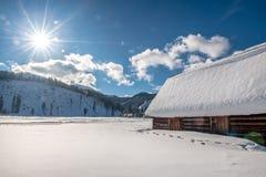 Casa de madeira velha pela estrada em um cenário bonito do inverno Sol belamente iluminado no fundo fotos de stock