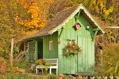 Casa de madeira verde do jardim no por do sol Imagem de Stock