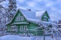 Casa de madeira verde no inverno na vila do russo imagem de stock