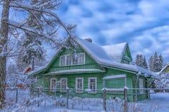Casa de madeira verde no inverno na vila do russo fotografia de stock royalty free