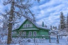 Casa de madeira verde no inverno na vila do russo imagens de stock