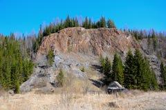 Casa de madera abandonada debajo de la roca Foto de archivo libre de regalías