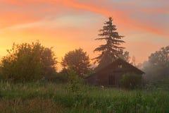Casa de madera abandonada en la salida del sol Imágenes de archivo libres de regalías