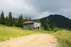 Casa de madera cerca del camino Imagen de archivo