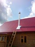Casa de madera con la chimenea en el tejado de teja Fotos de archivo libres de regalías
