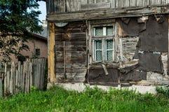 Casa de madera, dañada vieja con la ventana Fotos de archivo libres de regalías