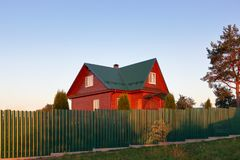 Casa de madera debajo de la casa verde del tejado del metal detrás de los lihgts verdes de la puesta del sol de la cerca fotos de archivo