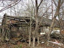 Casa de madera destruida abandonada en peque?o pueblo ruso imagenes de archivo