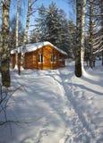 Casa de madera en bosque del invierno Foto de archivo libre de regalías
