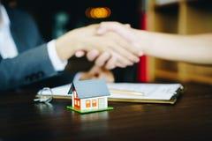 Casa de madera en el fondo de la tabla con los agentes inmobiliarios y el cliente que sacuden las manos después de firmar el cont fotografía de archivo libre de regalías