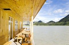 Casa de madera en el lago cerca de la montaña Foto de archivo
